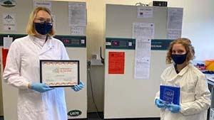 Two people stand at a distance in a lab facing the camera, both wearing face masks. One holds the Biobank of the Year Award certificate while the other holds the tropy