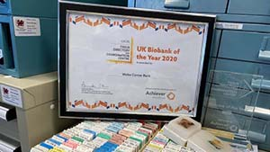 Framed Biobank of the Year Award certificate perched above open drawer of paraffin embedded tissue samples. The clear award trophy is placed to the right of the certificate