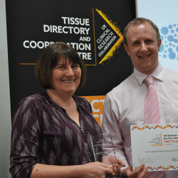 Sue Ring and Phil Quinlan posing with award and certificate