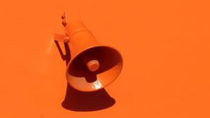 Orange conical speaker mounted on an orange wall